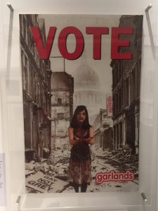 Garlands poster reading VOTE and showing a drag queen
