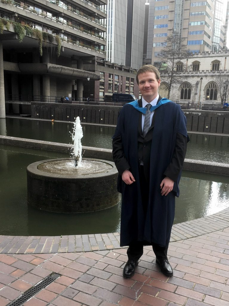 Robert in his graduation robes in front of a fountain at the Barbican Centre