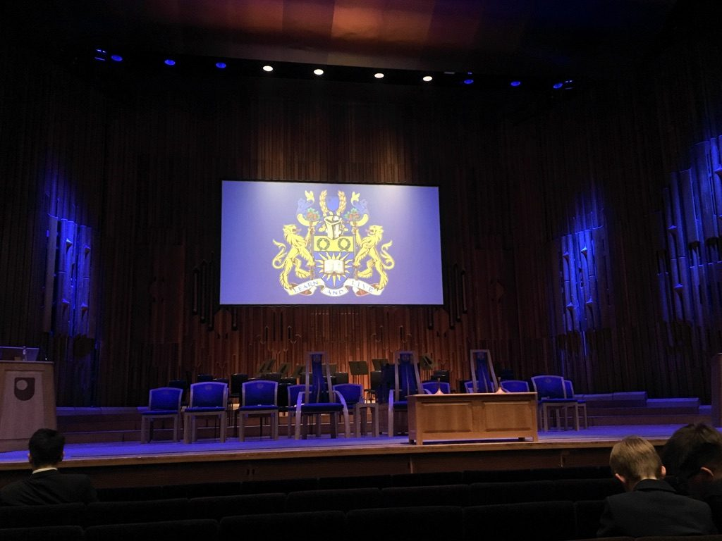 Photo of main hall at the Barbican Centre with OU crest displayed