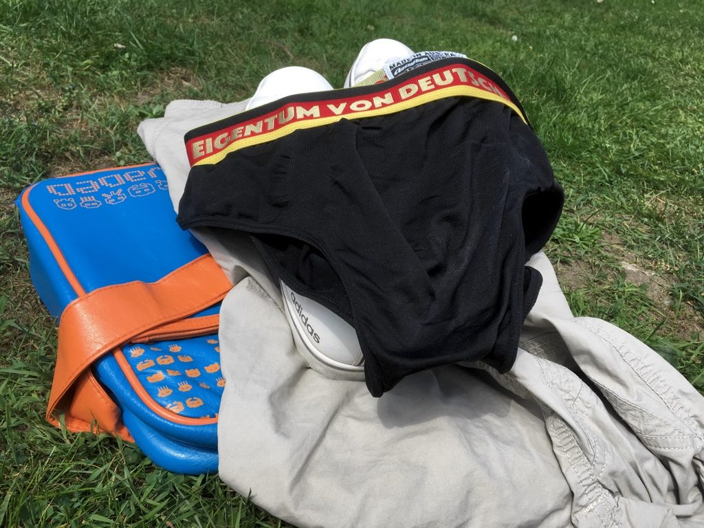 Shoes, shorts, t-shirt and underpants on a patch of grass
