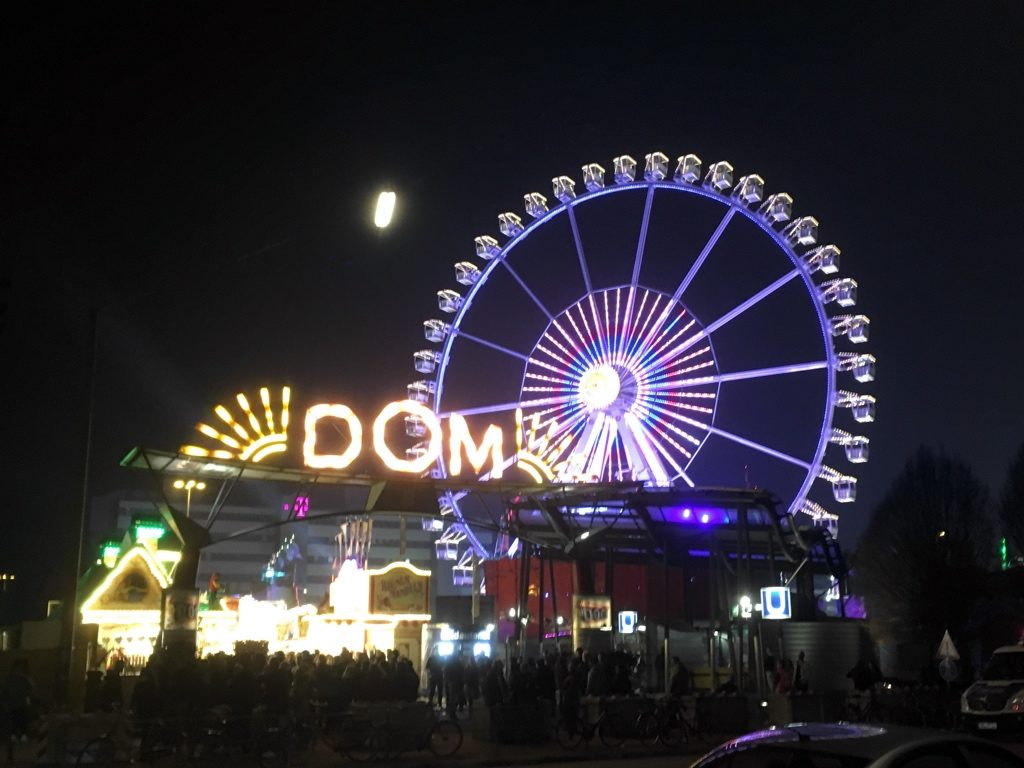 Entrance to Hamburg Dom fair and Ferris Wheel, at night