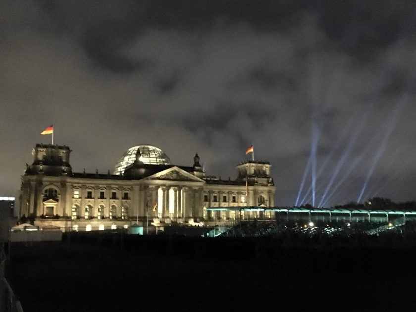 Photo of Reichstag building lit up at night, with spotlights from the Mauerfall concert in the background