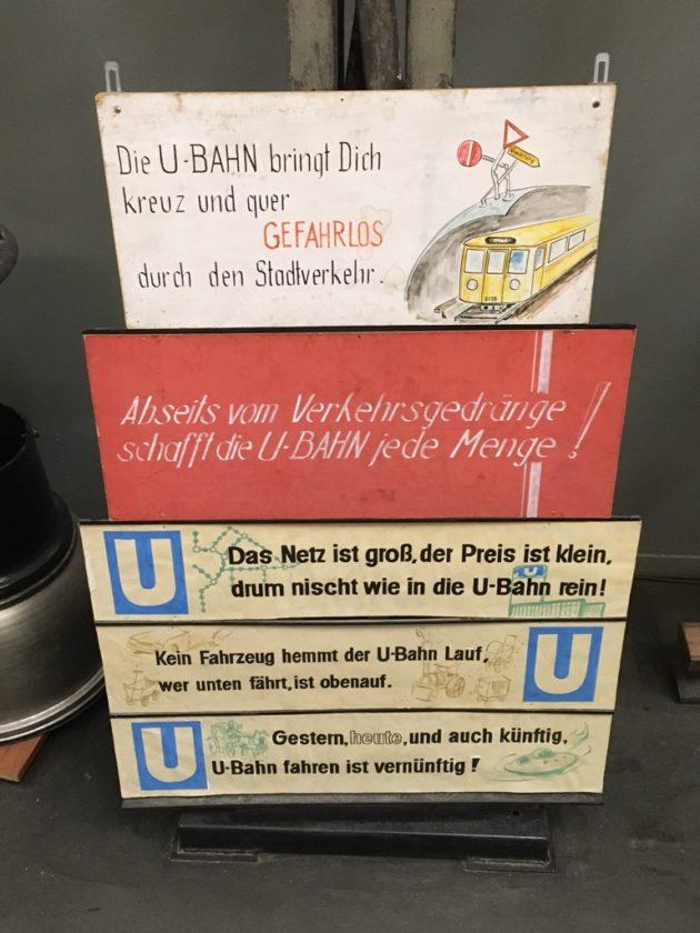 """Photo of signs bearing U-Bahn slogans: """"Die U-Bahn bringt Dich kreuz und quer / Gefharlos durch den Stadtverkehr"""" """"Abseits vom Verkehrsgedränge / schafft die U-Bahn jede Menge!"""" """"Das Netz ist groß, der Preis ist klein, / drum nischt wie in die U-Bahn rein!"""" """"Kein Fahrzeug hemmt der U-Bahn Lauf, / wer unten fährt, ist obenauf."""" """"Gestern, heute, unt auch künftig, U-Bahn fahren ist vernünftig!"""""""