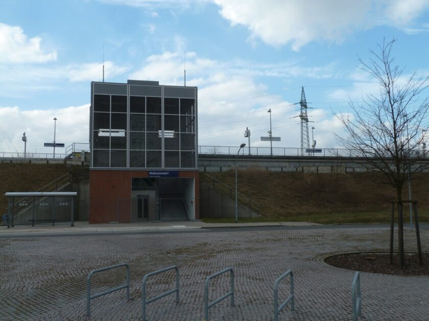 Waßmannsdorf station entrance, car park in foreground and platforms on an embankment